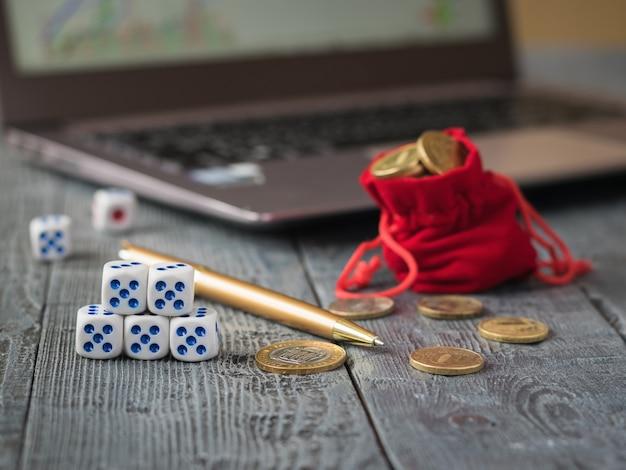 Kości i stos monet przed laptopem z harmonogramami biznesowymi.