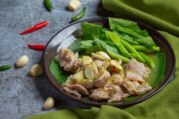 Kości wieprzowe tom yum tajskie jedzenie, żeberka wieprzowe tom yum ozdobione składnikami.