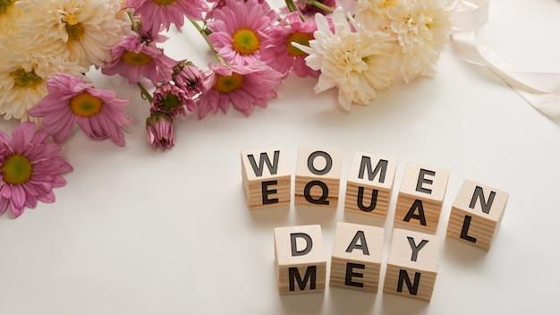 """Kości z napisem """"dzień kobiet"""" i """"równi mężczyźni"""" na białym stole ozdobionym różowymi kwiatami i miejscem na kopię"""