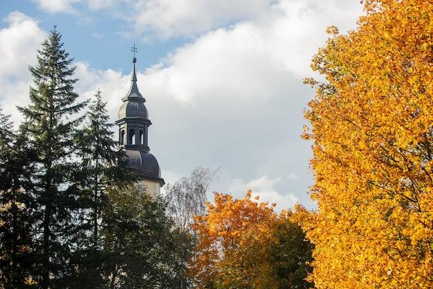 Kościół dzwonnica pośrodku jesiennych drzew