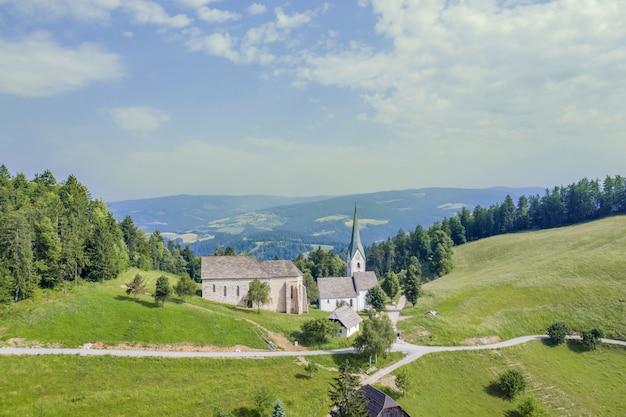 Kościół lese na polu otoczonym wzgórzami pokrytymi zielenią w słowenii