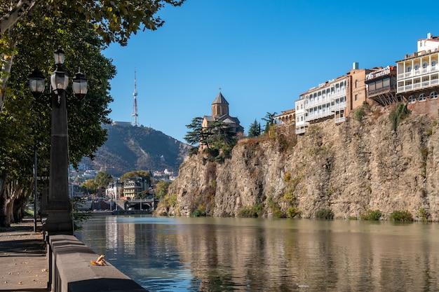 Kościół metekhi i domy na skraju urwiska nad rzeką kurą. tbilisi, historyczne centrum miasta