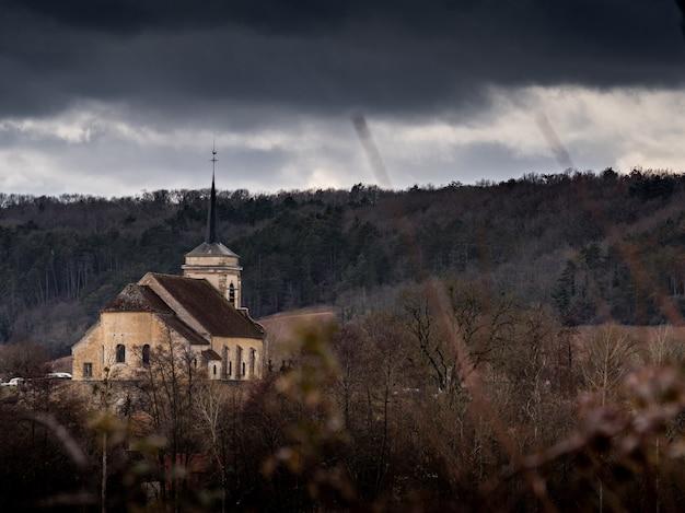 Kościół na wzgórzu otoczony zalesionymi wzgórzami pod pochmurnym niebem