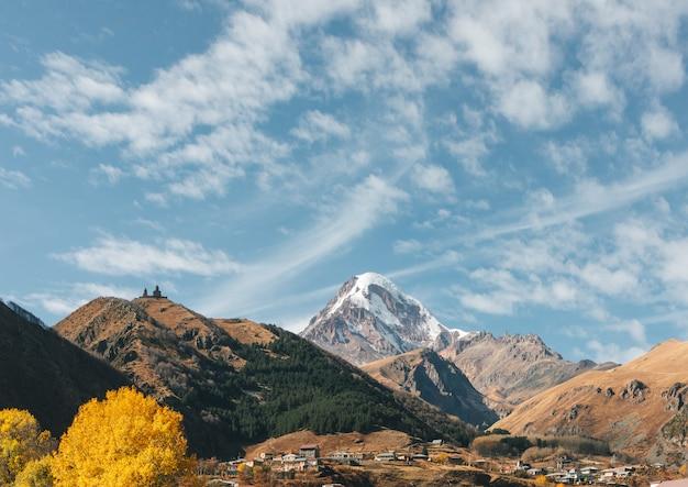 Kościół trójcy gergeti znany jako tsminda sameba na tle grzbietu górskiego i chmur, stepantsminda, kazbegi, georgia.