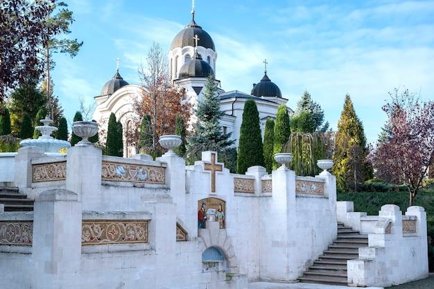 Kościół w klasztorze curchi. schody ze studnią i bujną zielenią. dobra pogoda w mołdawii