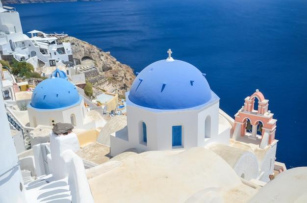 Kościół z błękitną kopułą przy santorini wyspą