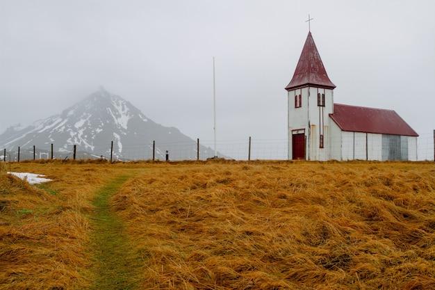 Kościół z czerwonym dachem w polu otoczonym skałami pod pochmurnym niebem w islandii