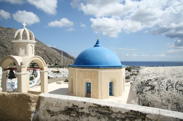 Kościół z niebieską kopułą pod słońcem i błękitnym pochmurnym niebem na santorini, grecja