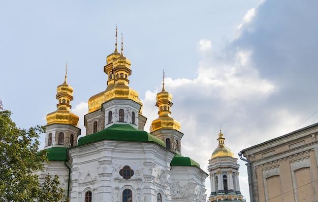Kościoły i złote kopuły w kijowie na ukrainie. prawosławna katedra chrześcijańska ze złotymi kopułami i krzyżami. kościół zbawiciela na berestowie, ławra kijowsko-peczerska