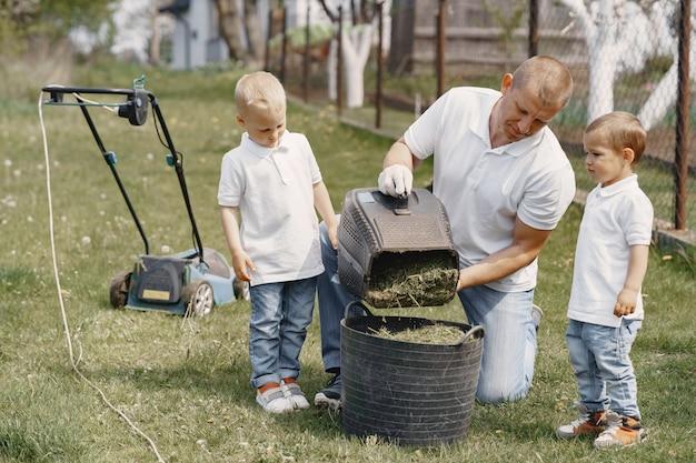 Kosiarka mężczyzna pracujący na podwórku z synami