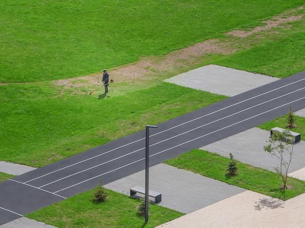 Kosiarka, usługi komunalne pracują na zielonym polu na dziedzińcu