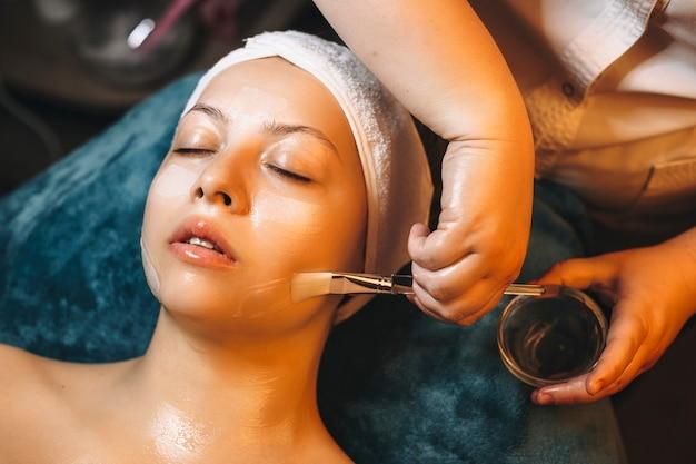 Kosmetolog dłoń trzymająca kubek z maseczką przeciwstarzeniową z kwasem hialuronowym i szczoteczką nakładającą maskę na kobiecą twarz w ośrodku wellness.