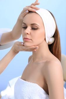 Kosmetolog, lekarz, bada skórę młodej dziewczyny. przygotowanie do zabiegu kosmetycznego.