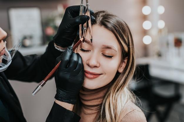 Kosmetolog mierzy linijką proporcje brwi. proces mikropigmentacji w gabinecie kosmetycznym.