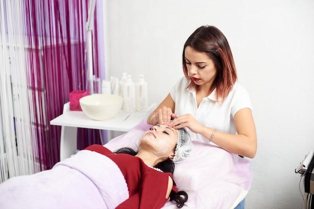 Kosmetolog nakłada krem i masuje kobietę