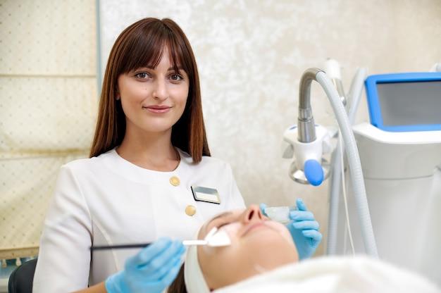 Kosmetolog nakłada maseczkę na twarz za pomocą pędzelka. zabieg upiększający. ochrona skóry.