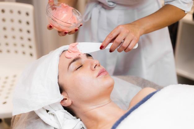 Kosmetolog nakłada maskę alginatową szpatułką na twarz kobiety.