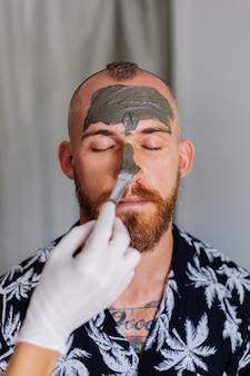 Kosmetolog nakłada szczoteczką maseczkę glinkową na twarz młodego przystojnego mężczyzny w gabinecie kosmetycznym
