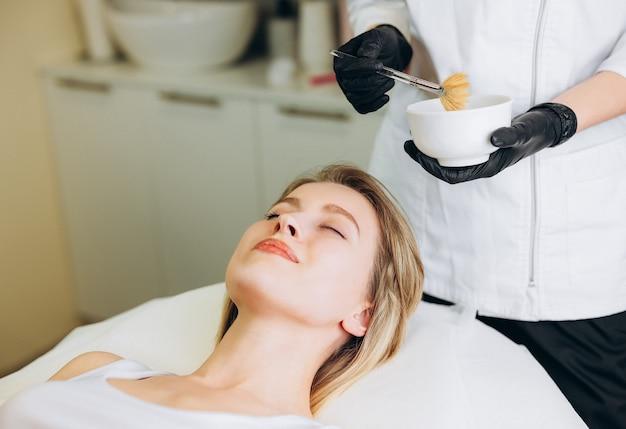 Kosmetolog nakłada szczoteczką peeling chemiczny kobiecej twarzy.
