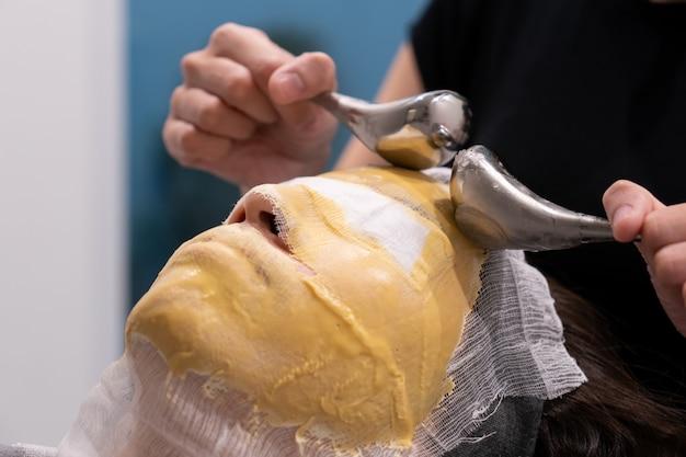 Kosmetolog nakłada złotą maskę na twarz, dzięki czemu skóra jest nawilżona i promienna.