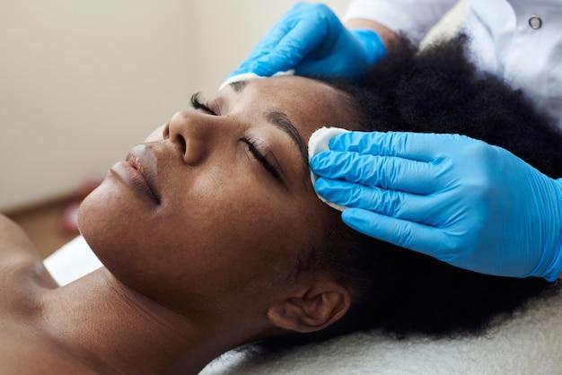 Kosmetolog oczyszcza tonikiem skórę twarzy pięknej, młodej kobiety w gabinecie kosmetycznym. ciemnoskóra modelka leży na kanapie u kosmetyczki.