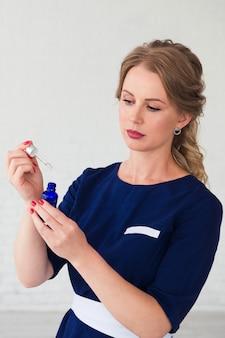 Kosmetolog przygotowuje się do zabiegu, serum przeciwstarzeniowe