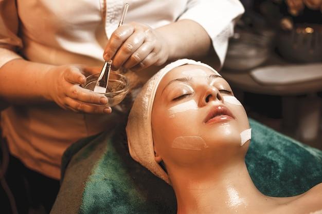 Kosmetolog ręcznie nakłada maskę z kwasem hialuronowym na kobiecą twarz w centrum odnowy biologicznej.