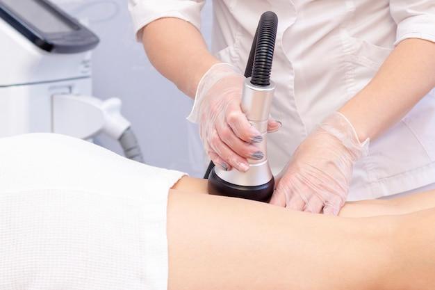 Kosmetolog redukujący cellulit na biodrach pacjentki, za pomocą maszyny do kawitacji ultradźwiękowej.