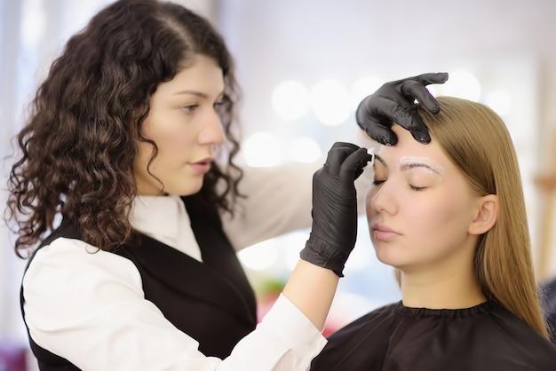 Kosmetolog robi brwi makijaż.