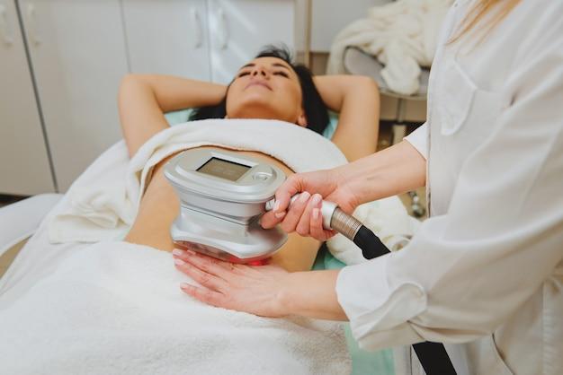 Kosmetolog robi masaż specjalnym aparatem na kobiecym brzuchu.