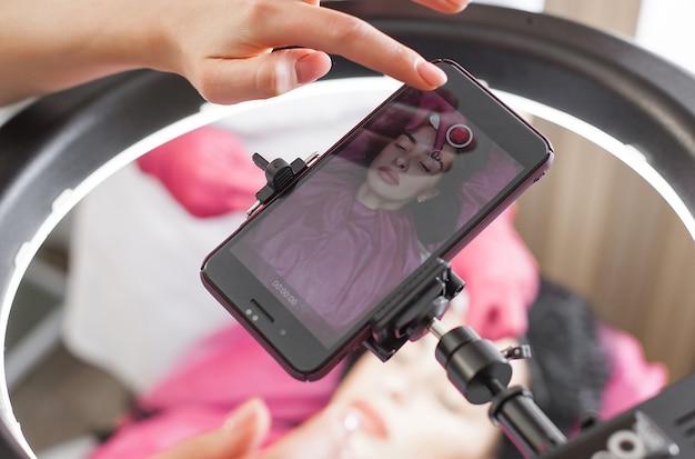 Kosmetolog robi portret na smartfonie swojego pacjenta. jeszcze przed / po zabiegu powiększania ust i iniekcji kolagenu.