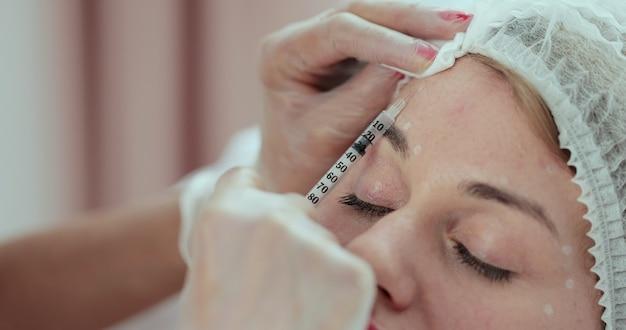 Kosmetolog robi zastrzyk z botoksu w czoło. kosmetyczka w rękawiczkach trzyma strzykawkę gotową do wstrzyknięcia piękna w kobiece czoło.