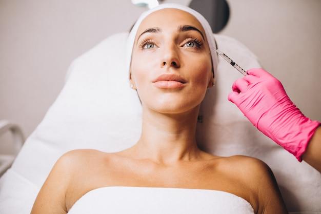 Kosmetolog robi zastrzyki na twarz kobiety w salonie piękności
