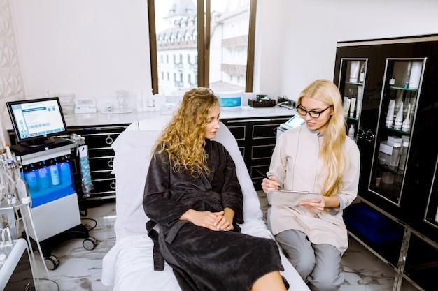 Kosmetolog rozmawia z pacjentką w nowoczesnej klinice spa. wybór procedury. portret atrakcyjna dama patrzeje broszurę w szarym szlafroku, podczas gdy kosmetolog opowiada o usługach salonowych