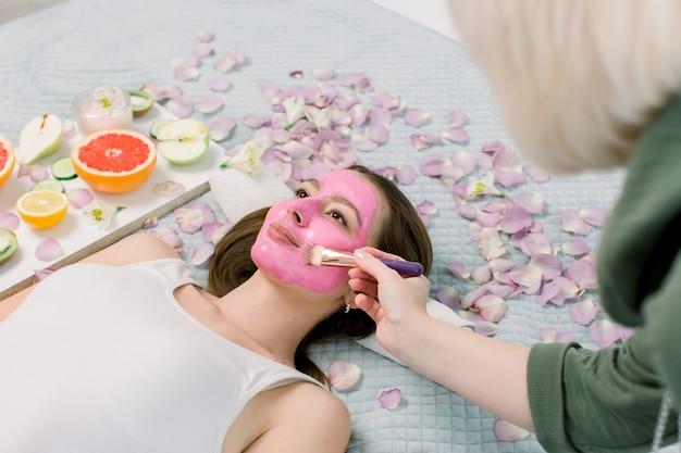 Kosmetolog rozmazuje kosmetyczną maskę na twarz ładnej młodej kobiety w salonie spa. maska na twarz, zabiegi kosmetyczne w spa, pielęgnacja skóry.