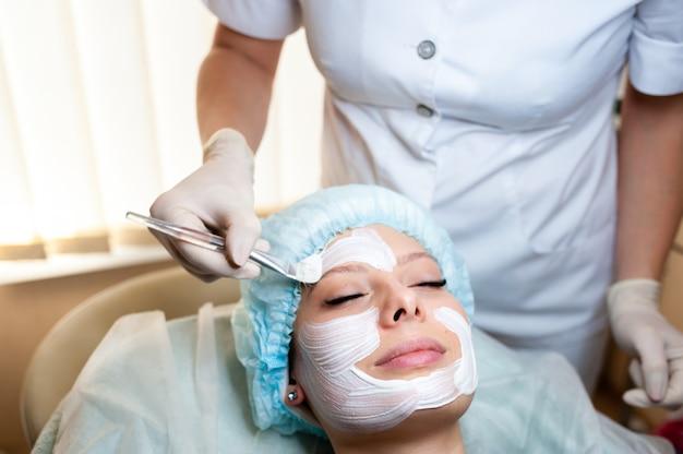 Kosmetolog sprawia, że maska jest piękną dziewczyną