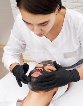 Kosmetolog stosujący czarną maskę na twarzy pięknej kobiety na skórki węglowe