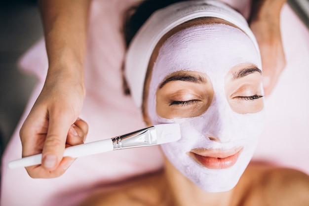 Kosmetolog stosuje maskę na twarzy klienta w salonie piękności