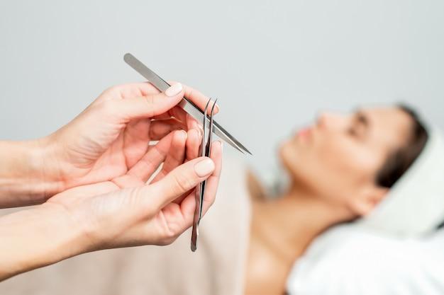 Kosmetolog trzyma pincety do przedłużania rzęs.