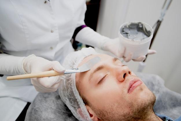 Kosmetolog w gabinecie kosmetycznym nakłada czarną maskę na twarz młodego mężczyzny.
