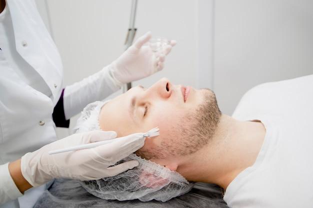Kosmetolog w gabinecie kosmetycznym nakłada na twarz młodego mężczyzny odżywianie liftingujące, aby wygładzić ją i usunąć blizny oraz zmarszczki.