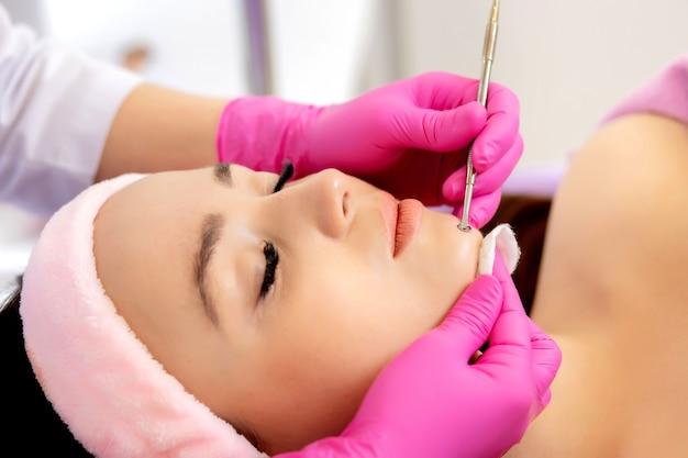 Kosmetolog w gabinecie kosmetycznym spa robi leczenie trądziku za pomocą przyrządu mechanicznego. koncepcja leczenia odmładzania i pielęgnacji skóry.