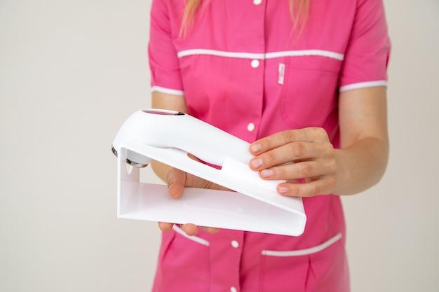 Kosmetolog w różowym mundurze trzyma w dłoniach urządzenie laserowe do pielęgnacji skóry twarzy i ciała. młodość i piękno. kosmetyka. dermatologia. narzędzia kosmetyczki. piękno.