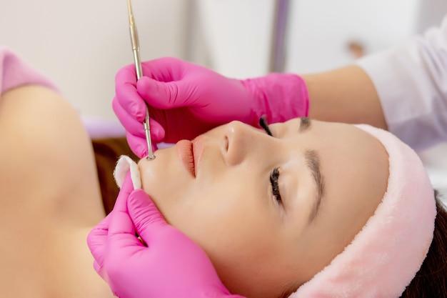 Kosmetolog w salonie kosmetycznym spa wykonuje leczenie trądziku przy użyciu instrumentu mechanicznego.
