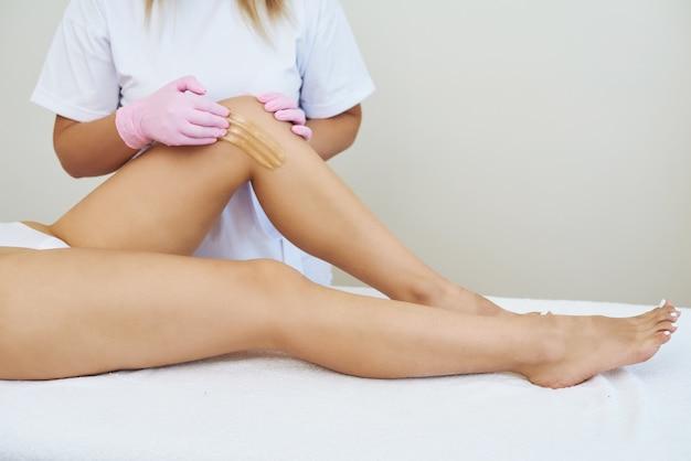 Kosmetolog woskowanie nóg kobiety