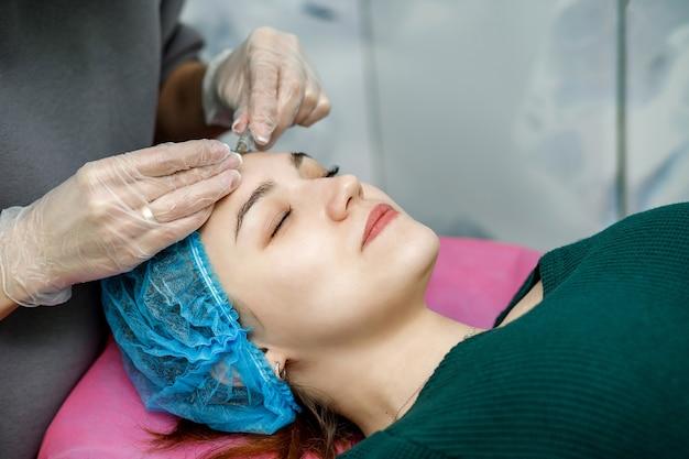Kosmetolog wstrzykuje twarz młodej dziewczynie leżącej na kanapie