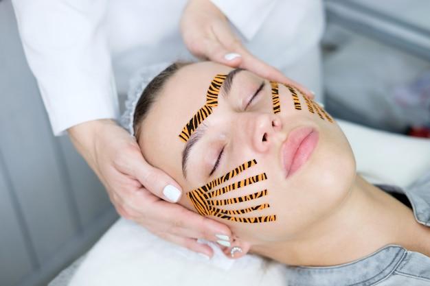 Kosmetolog wykonujący taśmę na twarzy za pomocą taśm w kolorze tygrysa w gabinecie kosmetycznym