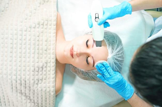 Kosmetolog wykonujący ultrasonograficzny peeling twarzy dla młodej kobiety, widok powyżej