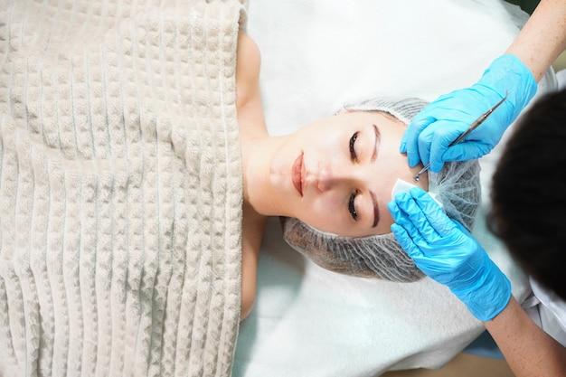 Kosmetolog wykonujący zabieg mechanicznego oczyszczania twarzy młodej kobiety