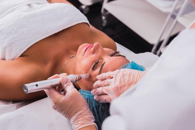 Kosmetolog wykonujący zabieg mezoterapii iniekcyjnej dermapenem na twarzy dorosłej kobiety w celu odmłodzenia w centrum spa.
